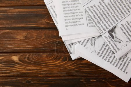 top view of pile of newspapers on wooden background with copy space