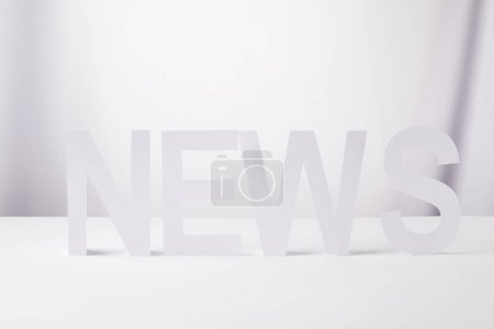 minimalistic word news made of paper, on white background