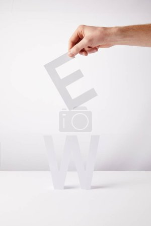 cropped view of person holding paper letters - e and w, on white background
