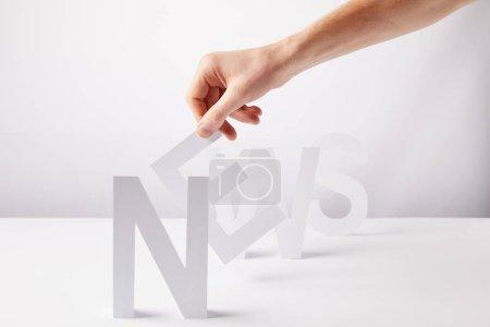 recadrée vue de la personne qui détient des lettres de papier - nouvelles de mot, sur fond blanc