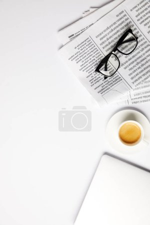 flat lay with eyeglasses, coffee, laptop and newspapers, on white with copy space