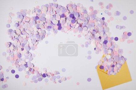 top view of violet confetti pieces and yellow envelope on surface
