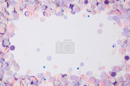 top view of frame of violet confetti pieces on white surface