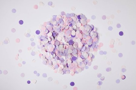 top view of pile of violet confetti pieces on white surface