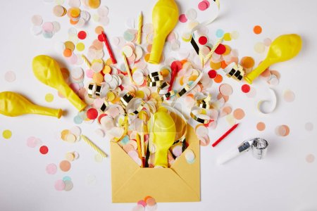 Photo for Top view of confetti pieces, balloons and yellow envelope on white surface - Royalty Free Image