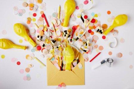 Photo pour Vue de dessus des morceaux de confettis, des ballons et de l'enveloppe jaune sur la surface blanche - image libre de droit