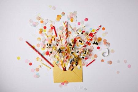 Photo pour Vue de dessus des morceaux de confettis et enveloppe jaune sur la surface blanche - image libre de droit