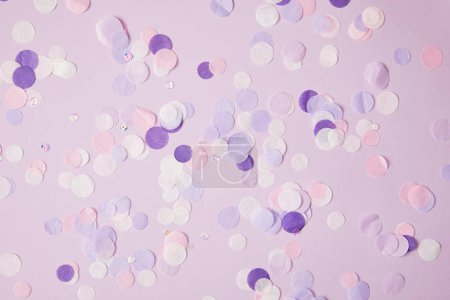 top view of scattered violet confetti pieces on surface