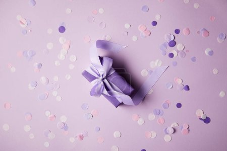 top view of one violet gift box and confetti pieces on surface