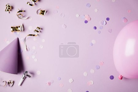 top view of confetti pieces, balloon and party hat on violet surface