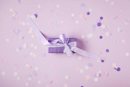 top view of one violet present box and confetti pieces on surface