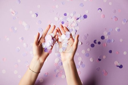 cropped image of woman holding falling confetti pieces on surface