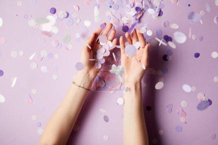 Foto de Imagen recortada de mujer cogida cae confeti piezas superficie - Imagen libre de derechos
