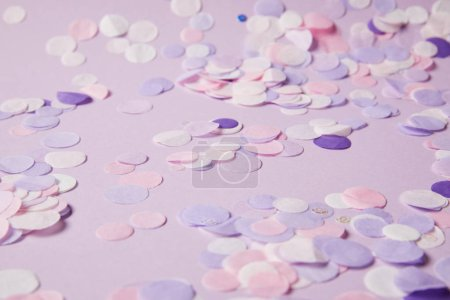 selective focus of confetti pieces on violet surface