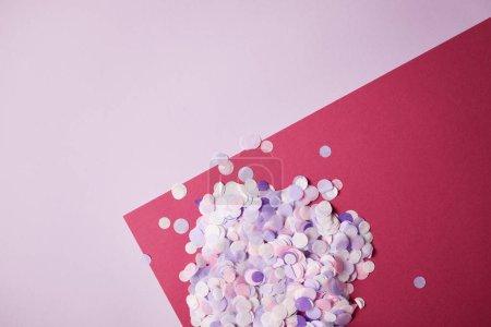 vista superior de piezas de confetti sobre superficie roja y violeta