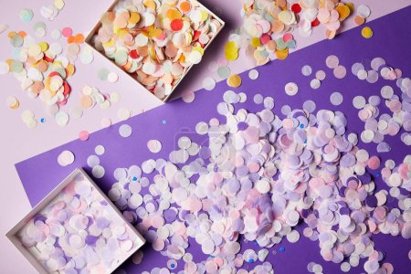 elevated view of confetti pieces in paper boxes and violet surface