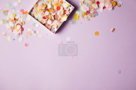 Foto de Vista superior de piezas de confeti en caja de papel y superficie violeta - Imagen libre de derechos