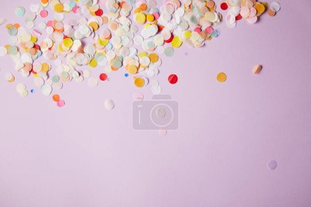 top view of tiny confetti pieces on violet surface