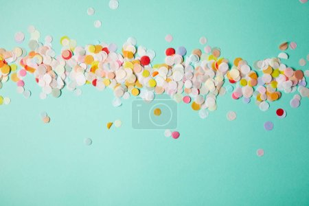 Photo pour Vue de dessus des morceaux de confettis sur la surface turquoise - image libre de droit