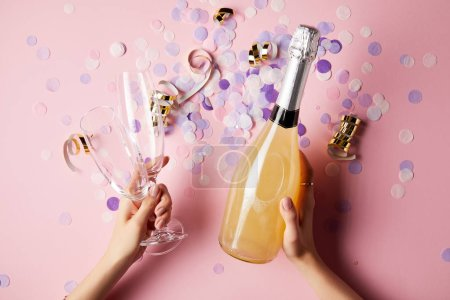 Photo for Cropped image of woman holding bottle of champagne and glasses above confetti on party table - Royalty Free Image