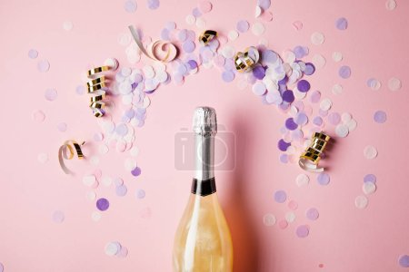 top view of bottle of champagne and confetti pieces on pink surface