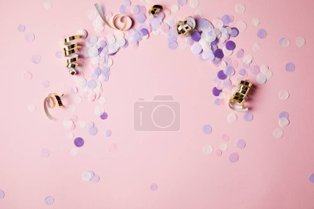 Photo for Elevated view of violet confetti pieces on pink surface - Royalty Free Image