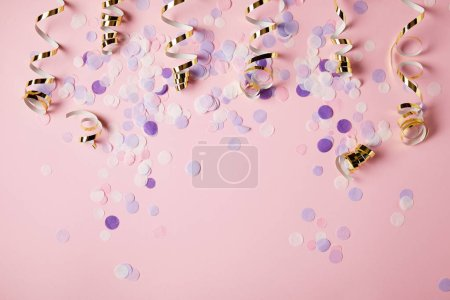 top view of violet confetti pieces on pink surface