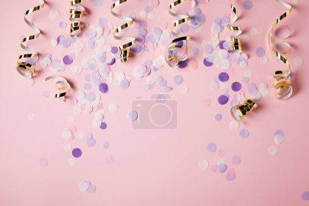 Photo pour Vue de dessus des morceaux de confettis violets sur la surface rose - image libre de droit