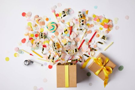 top view of gift box and scattered confetti pieces on white surface