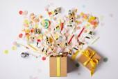 """Постер, картина, фотообои """"вид сверху подарочной коробке и рассеянного конфетти штук на белой поверхности"""""""