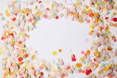 top view of colored confetti pieces on white surface
