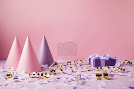 party hats, gift box and confetti pieces on violet tabletop