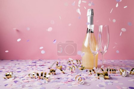 bottle of champagne, glasses and falling confetti pieces on violet surface