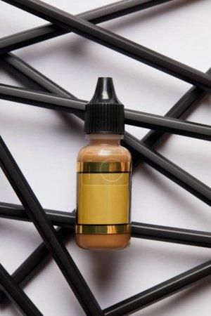 Photo pour Vue du dessus de la bouteille cosmétique avec étiquette vierge et outils pour un maquillage permanent sur blanc - image libre de droit