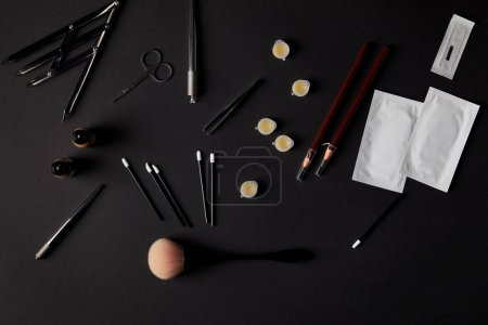 top view of brushes, pencils, cosmetics and tools for permanent makeup on black