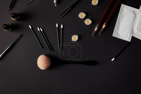 top view of various brushes, pencils and tools for permanent makeup on black