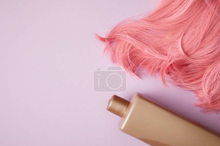 top view of bright pink wig and blank container on purple