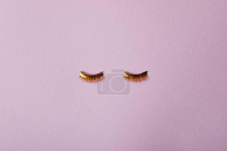 Photo pour Vue de dessus de faux cils dorés élégants isolés sur violet - image libre de droit