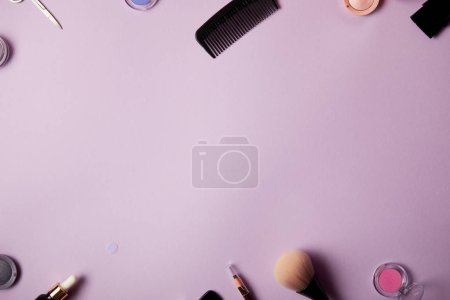 top view of various makeup tools and cosmetics on purple background