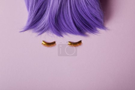 top view of bright violet wig and false golden eyelashes on purple