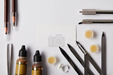 top view of various tools and make up pencils for permanent makeup and blank card on white