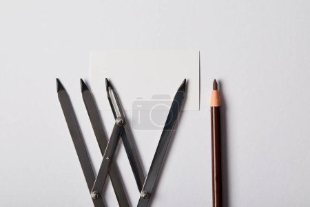 top view of tools for permanent makeup and blank card on white