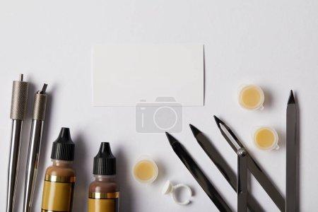 Photo pour Vue du dessus des outils pour le maquillage permanent et le papier blanc isolé sur blanc - image libre de droit