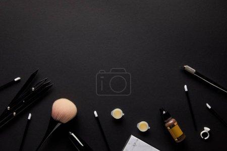 Photo pour Vue surélevée des outils pour un maquillage permanent isolé sur noir - image libre de droit