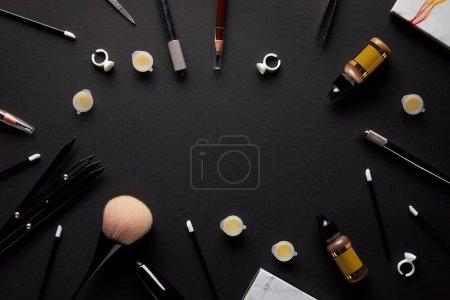 Photo pour Vue du dessus des outils pour le maquillage permanent sur table noire dans le salon - image libre de droit