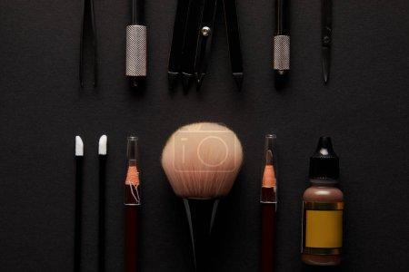 Photo pour Pose plate de crayons et pinceaux pour un maquillage permanent isolé sur noir - image libre de droit