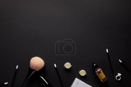 Photo pour Vue de dessus des outils pour un maquillage permanent isolé sur noir - image libre de droit