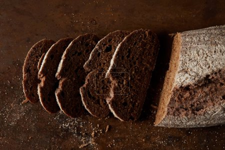 elevated view of bred and slices of bread on rustic metal tabletop