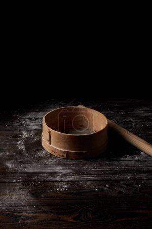 Photo for Close up view of sieve and rolling pin on wooden table covering by flour isolated on black background - Royalty Free Image