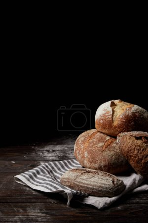 Photo for Closeup image of various types of bread and sackcloth on wooden table covering by flour - Royalty Free Image